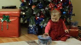 Μικρό παιδί με το επόμενο ot κιβωτίων καραμελών ένα χριστουγεννιάτικο δέντρο φιλμ μικρού μήκους