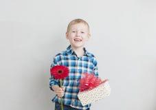 Μικρό παιδί με το κόκκινα λουλούδι και το δώρο Στοκ Φωτογραφία