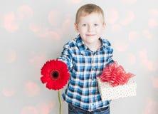 Μικρό παιδί με το κόκκινο κιβώτιο λουλουδιών και δώρων Στοκ Φωτογραφίες