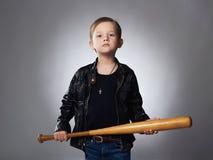 Μικρό παιδί με το ρόπαλο του μπέιζμπολ Αστείο παιδί στο παλτό δέρματος κακοποιός Στοκ εικόνα με δικαίωμα ελεύθερης χρήσης