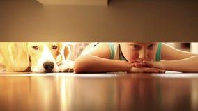 Μικρό παιδί με το σκυλί λαγωνικών καλύτερων φίλων του κάτω από το κρεβάτι απόθεμα βίντεο