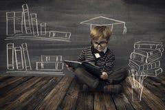 Μικρό παιδί παιδιών στα γυαλιά που διαβάζει το βιβλίο πέρα από το σχολικό μαύρο πίνακα