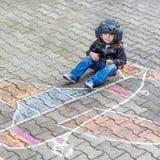 Μικρό παιδί που έχει τη διασκέδαση με το σχέδιο εικόνων αεροπλάνων με την κιμωλία στοκ φωτογραφία με δικαίωμα ελεύθερης χρήσης