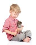 Μικρό παιδί που αγκαλιάζει ένα γατάκι η ανασκόπηση απομόνωσε το λευκό Στοκ Εικόνες