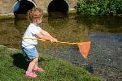 Μικρό παιδί που αλιεύει σε έναν ποταμό. Στοκ Εικόνα