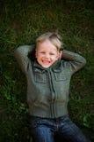 Μικρό παιδί που βρίσκεται στη χλόη και το γέλιο Στοκ Εικόνες