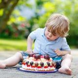 Μικρό παιδί που γιορτάζει τα γενέθλιά του στον εγχώριο κήπο με το μεγάλο ασβέστιο Στοκ Φωτογραφία