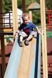 Μικρό παιδί που γλιστρά σε μια φωτογραφική διαφάνεια στοκ εικόνα
