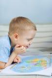 Μικρό παιδί που εξετάζει το χάρτη Στοκ φωτογραφία με δικαίωμα ελεύθερης χρήσης