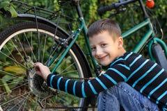 Μικρό παιδί που επισκευάζει το ποδήλατο Στοκ Εικόνες