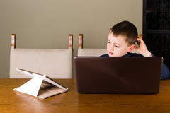 Μικρό παιδί που εργάζεται στην ταμπλέτα και το lap-top Στοκ εικόνα με δικαίωμα ελεύθερης χρήσης