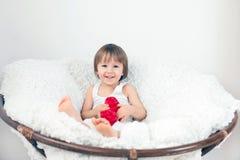 Μικρό παιδί, που κάθεται σε μια μεγάλη καρέκλα Στοκ εικόνες με δικαίωμα ελεύθερης χρήσης