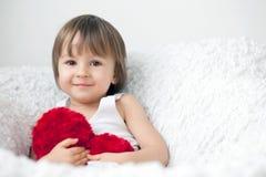 Μικρό παιδί, που κάθεται σε μια μεγάλη καρέκλα Στοκ Φωτογραφίες
