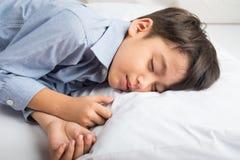 Μικρό παιδί που καθορίζει στο κρεβάτι το χαριτωμένο όμορφο πρόσωπο Στοκ Φωτογραφίες