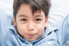 Μικρό παιδί που καθορίζει στο κρεβάτι το χαριτωμένο όμορφο πρόσωπο Στοκ φωτογραφία με δικαίωμα ελεύθερης χρήσης