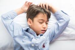Μικρό παιδί που καθορίζει στο κρεβάτι το χαριτωμένο όμορφο πρόσωπο Στοκ Φωτογραφία