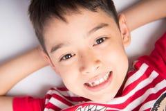 Μικρό παιδί που καθορίζει στο πάτωμα τη τοπ άποψη κοντά επάνω που χαμογελά Στοκ Εικόνες