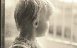 Μικρό παιδί που κοιτάζει από το παράθυρο κατά τη διάρκεια της βροχερής ημέρας στοκ φωτογραφία με δικαίωμα ελεύθερης χρήσης