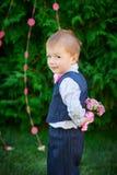 Μικρό παιδί που κρατά μια ανθοδέσμη των λουλουδιών πίσω από την πλάτη του Στοκ φωτογραφίες με δικαίωμα ελεύθερης χρήσης