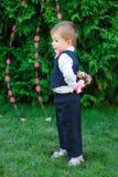 Μικρό παιδί που κρατά μια ανθοδέσμη των λουλουδιών στο πάρκο Στοκ Εικόνα