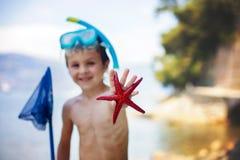 Μικρό παιδί που κρατά τον κόκκινο αστερία πέντε σημείου και καθαρός στα χέρια του στοκ εικόνες με δικαίωμα ελεύθερης χρήσης