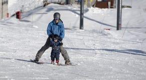 Μικρό παιδί που μαθαίνει να κάνει σκι με τον πατέρα του Στοκ Εικόνες