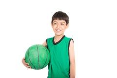 Μικρό παιδί που παίζει την πράσινη καλαθοσφαίριση στον πράσινο ομοιόμορφο αθλητισμό PE Στοκ Εικόνα