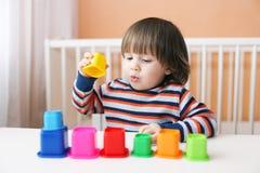 Μικρό παιδί που παίζει τους πλαστικούς φραγμούς Στοκ εικόνα με δικαίωμα ελεύθερης χρήσης