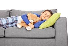 Μικρό παιδί που παίρνει ένα NAP σε έναν καναπέ στοκ εικόνες