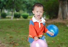 Μικρό παιδί που παίρνει δύο μπαλόνια στοκ φωτογραφία