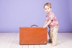 Μικρό παιδί που πηγαίνει σε ένα ταξίδι με τη βαλίτσα Στοκ φωτογραφία με δικαίωμα ελεύθερης χρήσης