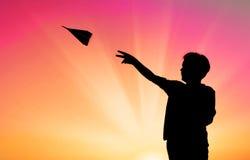 Μικρό παιδί που ρίχνει τη σκιαγραφία αεροπλάνων εγγράφου Στοκ Εικόνες