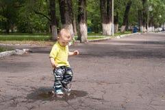Μικρό παιδί που τρέχει γύρω από τις λακκούβες Στοκ Φωτογραφίες