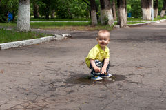 Μικρό παιδί που τρέχει γύρω από τις λακκούβες Στοκ φωτογραφίες με δικαίωμα ελεύθερης χρήσης