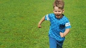 Μικρό παιδί που τρέχει πέρα από τον όμορφο πράσινο τομέα το καλοκαίρι, την πολύ ελαφριά και ευτυχή σκηνή φιλμ μικρού μήκους