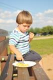 Μικρό παιδί που τρώει τις τηγανιτές πατάτες στοκ εικόνες
