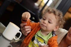 Μικρό παιδί που τρώει τον αφρό του καφέ στοκ φωτογραφία