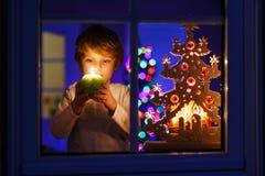 Μικρό παιδί που υπερασπίζεται το παράθυρο στο χρόνο Χριστουγέννων Στοκ φωτογραφία με δικαίωμα ελεύθερης χρήσης