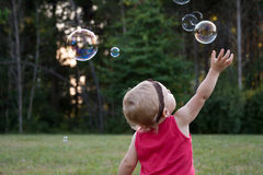 Μικρό παιδί που φθάνει για τις φυσαλίδες Στοκ εικόνα με δικαίωμα ελεύθερης χρήσης
