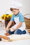 Μικρό παιδί που φορά τα καπέλα αρχιμαγείρων που ψήνουν μια πίτα Στοκ εικόνα με δικαίωμα ελεύθερης χρήσης