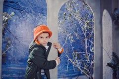 Μικρό παιδί που φορούν τα θερμά ενδύματα και orandge καπέλο υπαίθριο Στοκ Εικόνα