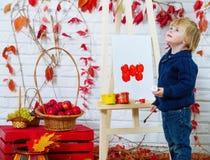 Μικρό παιδί που χρωματίζει τα κόκκινα μήλα στοκ φωτογραφίες