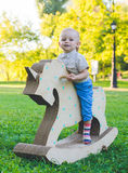 Μικρό παιδί σε έναν μονόκερο παιχνιδιών Χλοώδης τομέας στο πάρκο δέντρο πεδίων χαμόγελο αγοριών και he& x27 s ευτυχές Στοκ φωτογραφία με δικαίωμα ελεύθερης χρήσης