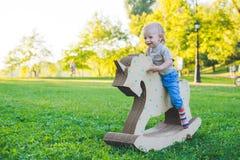 Μικρό παιδί σε έναν μονόκερο παιχνιδιών Χλοώδης τομέας στο πάρκο δέντρο πεδίων χαμόγελο αγοριών και he& x27 s ευτυχές Στοκ Φωτογραφία