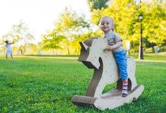 Μικρό παιδί σε έναν μονόκερο παιχνιδιών Χλοώδης τομέας στο πάρκο δέντρο πεδίων χαμόγελο αγοριών και he& x27 s ευτυχές Στοκ Εικόνα