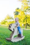 Μικρό παιδί σε έναν μονόκερο παιχνιδιών Χλοώδης τομέας στο πάρκο δέντρο πεδίων χαμόγελο αγοριών και he& x27 s ευτυχές Στοκ εικόνα με δικαίωμα ελεύθερης χρήσης