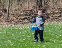 Μικρό παιδί σε ένα κυνήγι αυγών Πάσχας υπαίθρια Στοκ Εικόνες