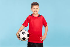 Μικρό παιδί σε ένα κόκκινο Τζέρσεϋ που κρατά ένα ποδόσφαιρο Στοκ Φωτογραφίες