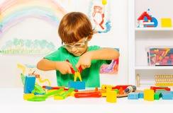 Μικρό παιδί στα γυαλιά που μαθαίνει να χρησιμοποιεί τις πένσες Στοκ Εικόνες