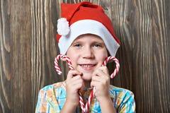 Μικρό παιδί στην κόκκινη ΚΑΠ με τον κάλαμο καραμελών Χριστουγέννων δύο Στοκ Φωτογραφία